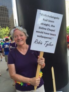 Andrea Bauman holding one of the parade signs
